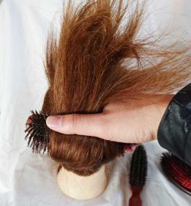 髪の毛を指とブラシで挟む